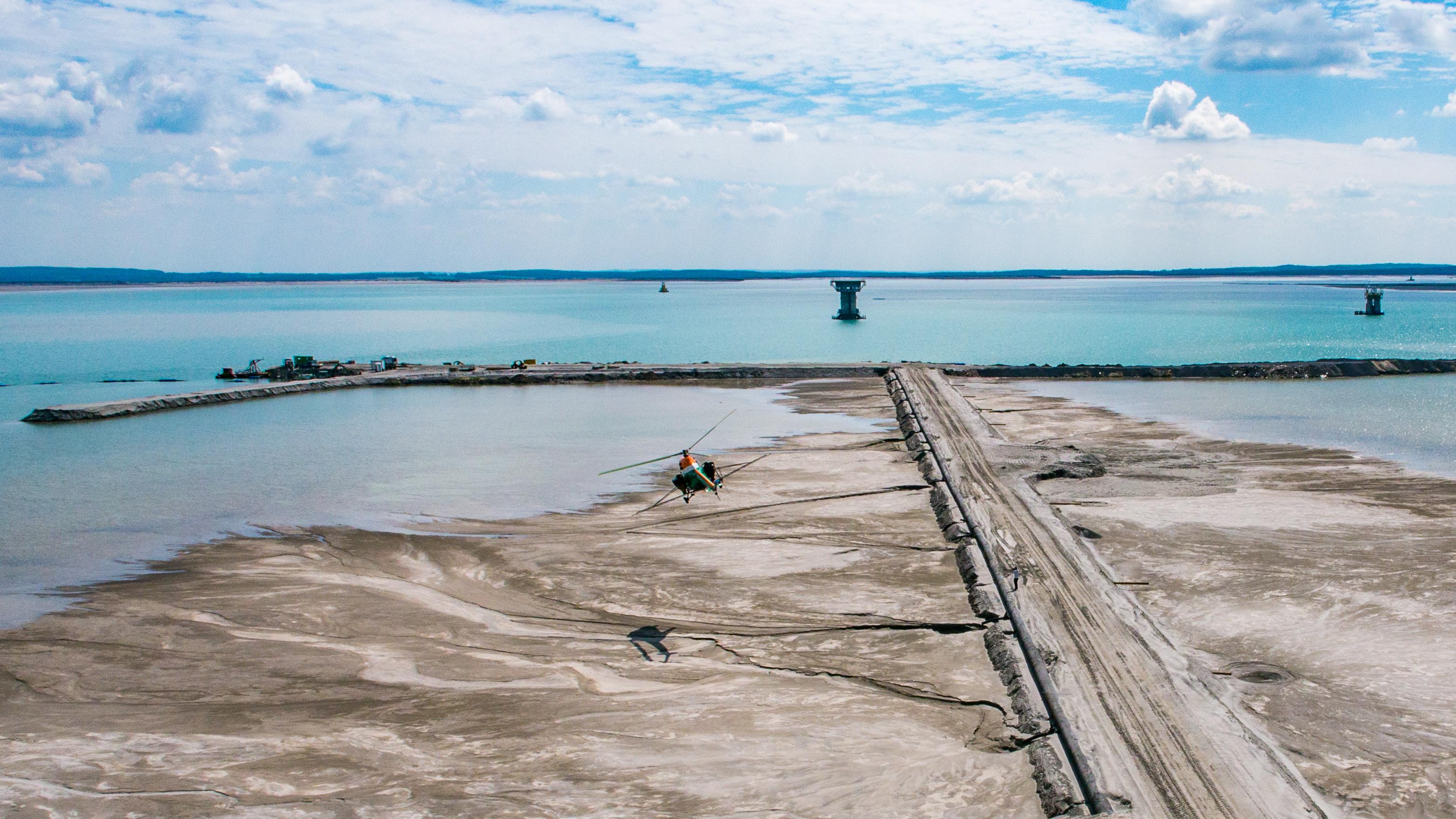 W centrum zdjęcia śmigłowiec wykorzystywany do zabezpieczania plaż roztworami emulsji asfaltowej.