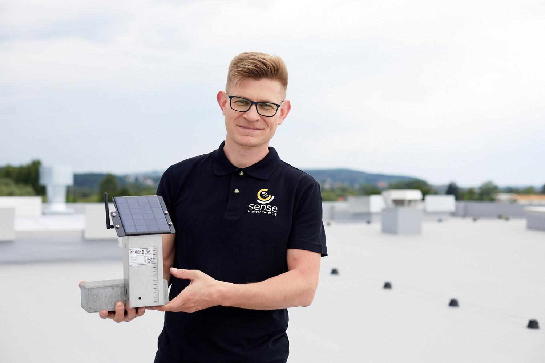 Artiom Komardin wraz z opracowanym przez Sense Monitoring detektorem spiętrzenia wody. Fot. mat. pras.